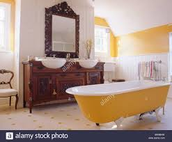 yellow roll top bath in yellow and white bathroom with ornate