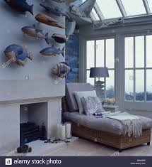 painted wooden fish sculptures on wall above fireplace in loft