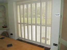 plantation shutters for sliding glass doors before a small garden