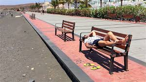 a guy sleeping lying down on the bench on the beach stock video