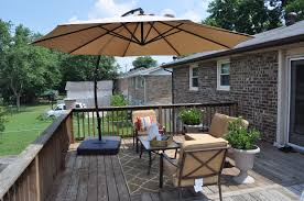 exterior brown deck umbrella over wooden table and chair on