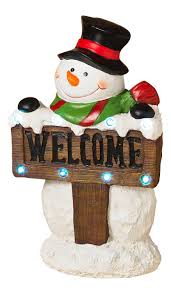 lighted santa and snowman decorations with welcome sign
