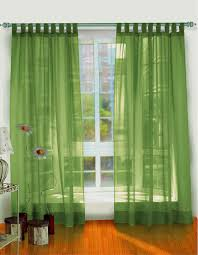 green fabric curtains on green hook connected by brown wooden