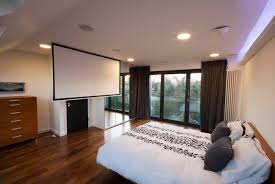 loft conversions bedroom with french doors and a cinema screen