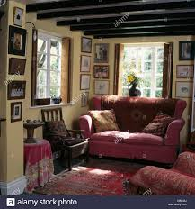 pink sofa in front of window in beamed cottage living room with
