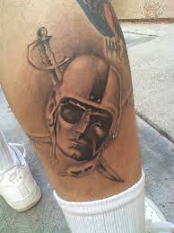 grey ink crossed swords and oakland raider face tattoo on leg
