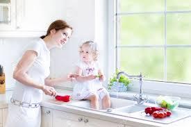 maman cuisine maman et ses adorables bouclés bébé fille laver les légumes