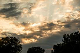 dramatic skies at sunset with clouds and sun rays image