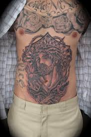 traditional jesus with dagger and cross tattoo on stomach tattoo wf