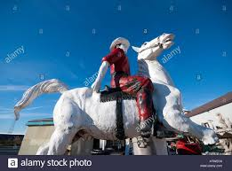 a well worn plaster sculpture of a cowboy and horse outside