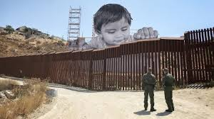 as boy peers curiously over border wall his artist asks u0027what is