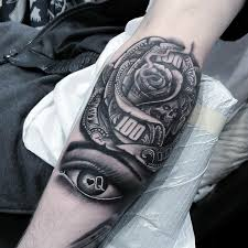 black and grey money rose with skull and eye tattoo on forearm