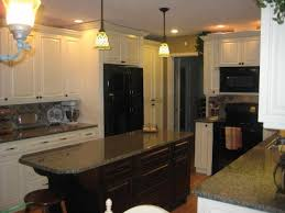 faced of light dark brown kitchen cabinets with black appliances
