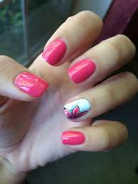 pink nails with a white ring finger that has a flower design on it
