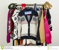 winter sweaters displayed on hangers with a big sale sign