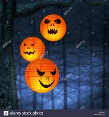 halloween paper lanterns hanging on a branch in a spooky and foggy
