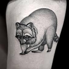 dotwork raccoon head tattoo on bicep by lauren sutton