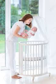 young mother putting her newborn baby to sleep in a white round