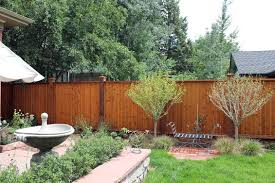 backyard with bird bath and wooden fences tips to installing