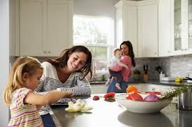 lesbienne dans la cuisine la fille utilise le comprimé dans la cuisine avec la maman l autre