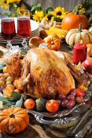 thanksgiving dinner roasted turkey on table with pumpkins
