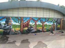 climbing wall mural the mural is a savannah setting with rocks trees and vines to climb surrounded by a rhino giraffe elephant tiger and turtle with exotic flowers