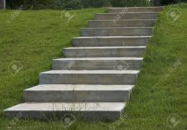 concrete steps looking up in lush green grass stock photo picture
