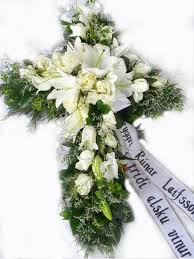 beautifuly decorated funeral cross with white flowers and greenery