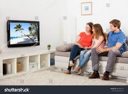 family watching tv living room stock photo 495040519 shutterstock