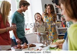 a family gathering for a meal adults and children around a table