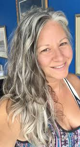 transitioning to gray hair with lowlights pretty long wavy gray hair on a real natural woman http