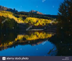 small pond reflects mountains and autumn colored trees in colorado