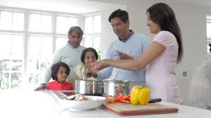 father preparing smoothie with his kids in kitchen at home stock