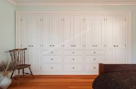 a solid wall of built in storage cabinets and warm fir floors in