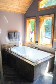 a luxurious two person bathtub rests under a wall of windows in a luxurious two person bathtub rests under a wall of windows in this rustic master