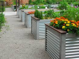 metal garden planters ideas with beautiful colorful flowers on the
