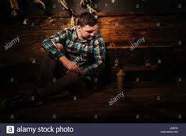 disappointed man sits near a chest holding glass bottle and