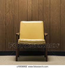 retro wood paneling stock photo of retro chair against wood paneling in office