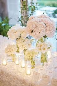 white flower centerpieces i each restroom there will be a cylinder vase with white