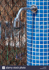swimming pool shower with blue mosaic tile column as the pool