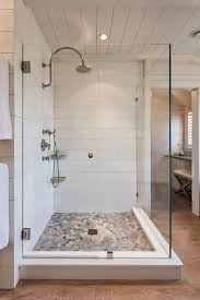 love the clean cottage look of this frameless glass enclosure with beach inspired pebble rock shower hardwood floors in bathroomshiplap