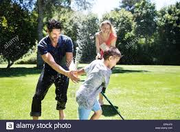 happy family garden happy family splashing water with garden hose stock photo royalty
