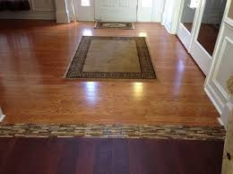 different wood floors in house with glass tile border flooring