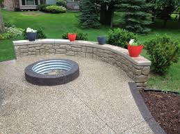 exposed aggregate with pre fab fire pit ring and rock face garden