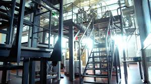 worker climb metal stairs at modern factory interior of milk