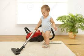 baby boy cleaning the carpet with vacuum cleaner stock photo