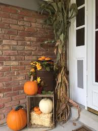 a porch dressed for fall with an old milk can corn stalks and a