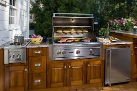 deck and outdoor kitchen with teak cabinets and built in grill