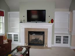 fireplace with built in bookcase and cabinet with glass doors plus