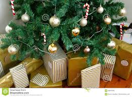 artificial christmas tree decorated with presents underneath stock
